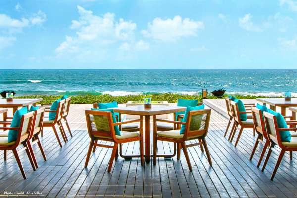 Dine outside by the ocean with seating featuring Sunbrella fabrics.