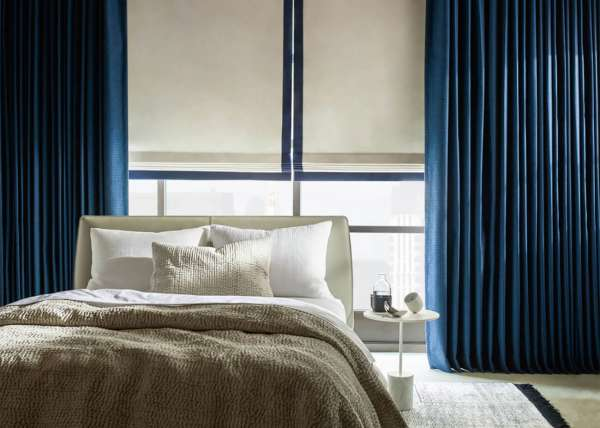 A hotel room and bed with blue drapery made with Sunbrella fabrics.