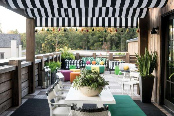 A deck with a black and white striped awning made with Sunbrella fabric.
