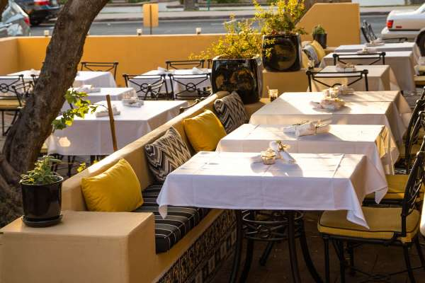 Restaurant outdoor patio seating with yellow fabric upholstery.