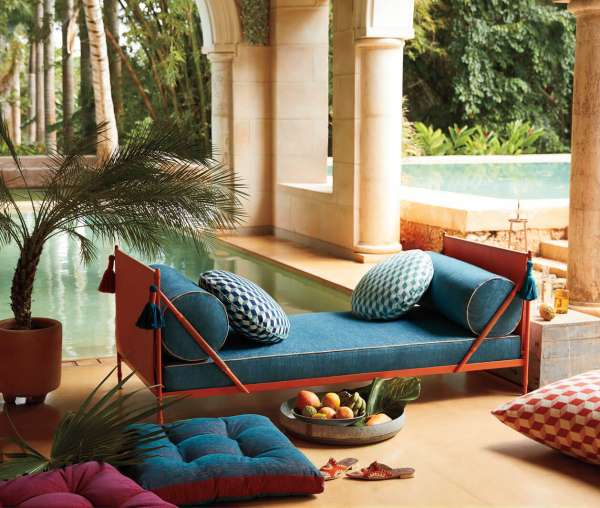 Sofa with blue Sunbrella fabric next to an outdoor pool.