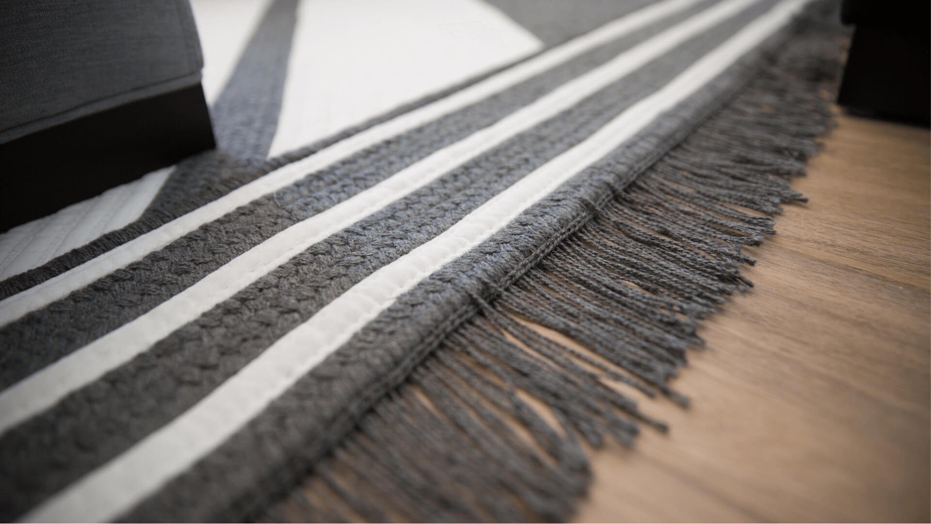 A grey and white striped Sunbrella Rug