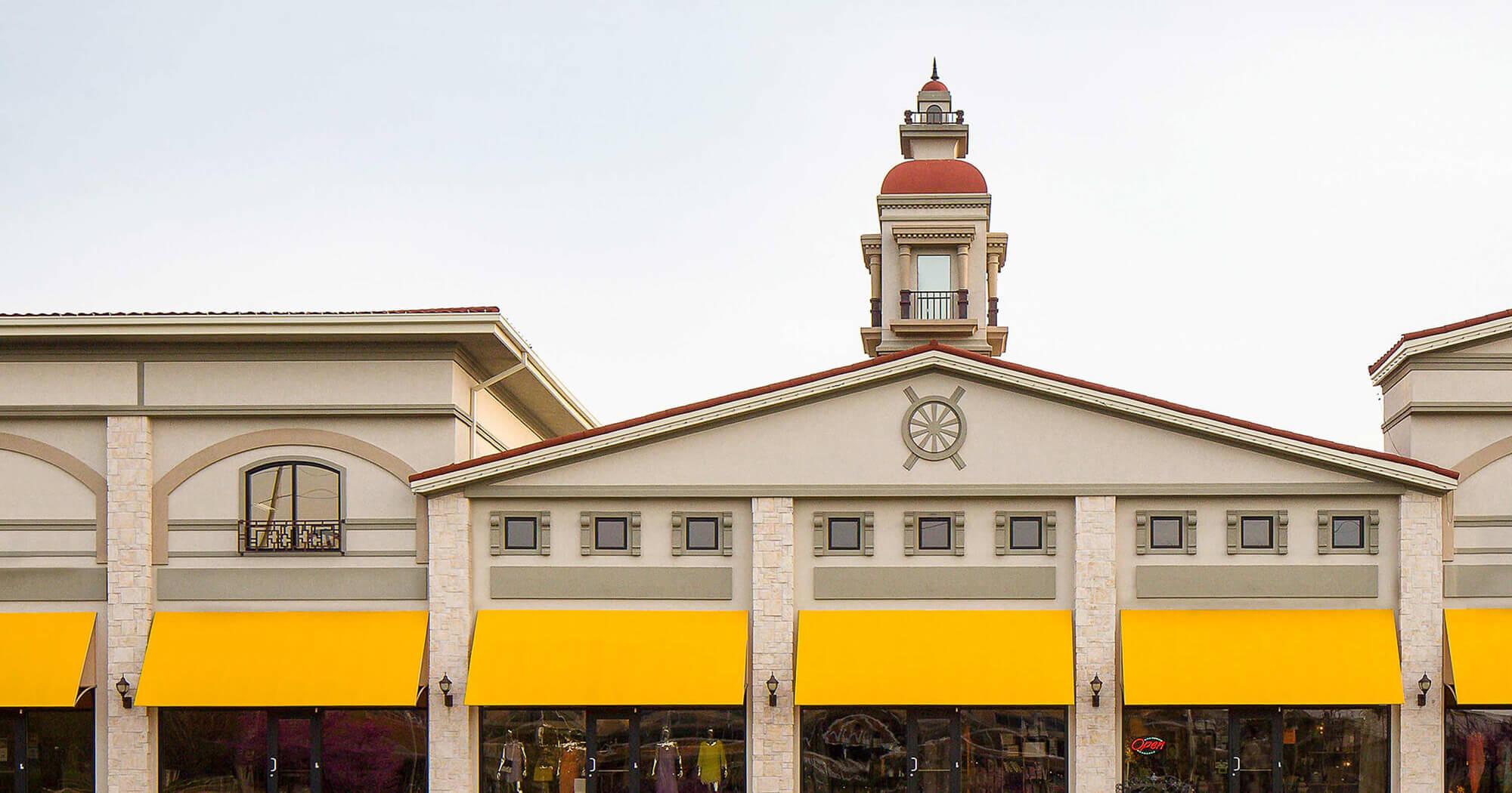 Um shopping center ganha um toque de cor com toldos feitos usando tecido de cobertura Sunbrella amarelo