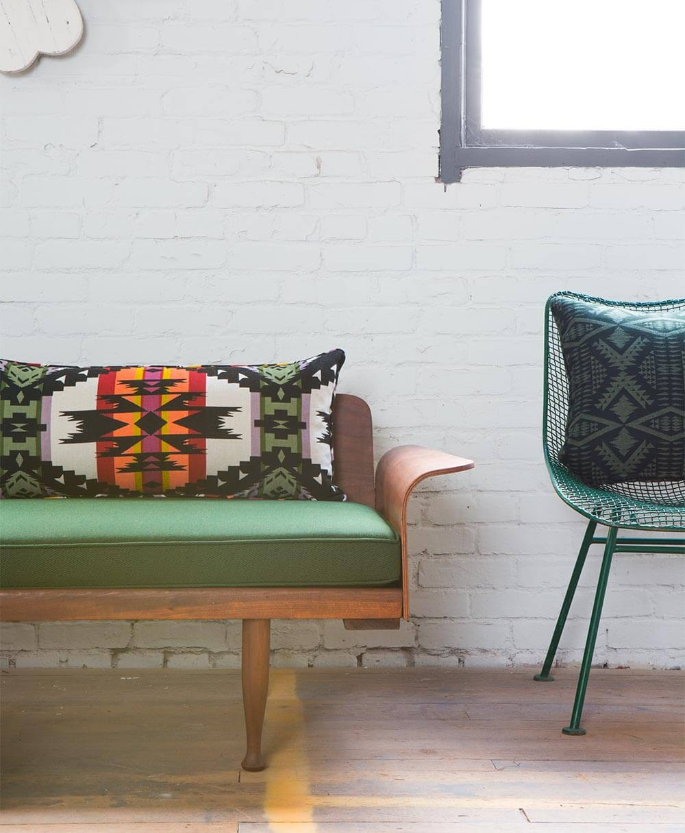 A wooden bench with green cushion is paired with a large lumbar pillow featuring Pendleton by Sunbrella fabrics.