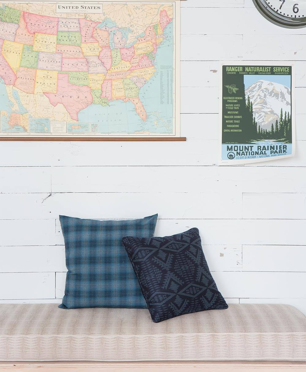 Blue patterned pillows sit on a beige patterned cushion, all fabrics from the Pendleton by Sunbrella collection.
