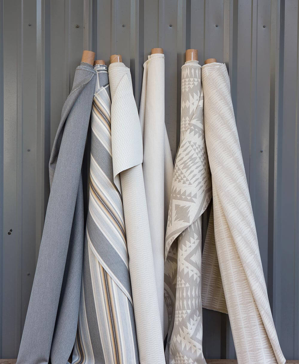 Rolls of neutral patterned Pendleton by Sunbrella upholstery fabrics lean against the wall.