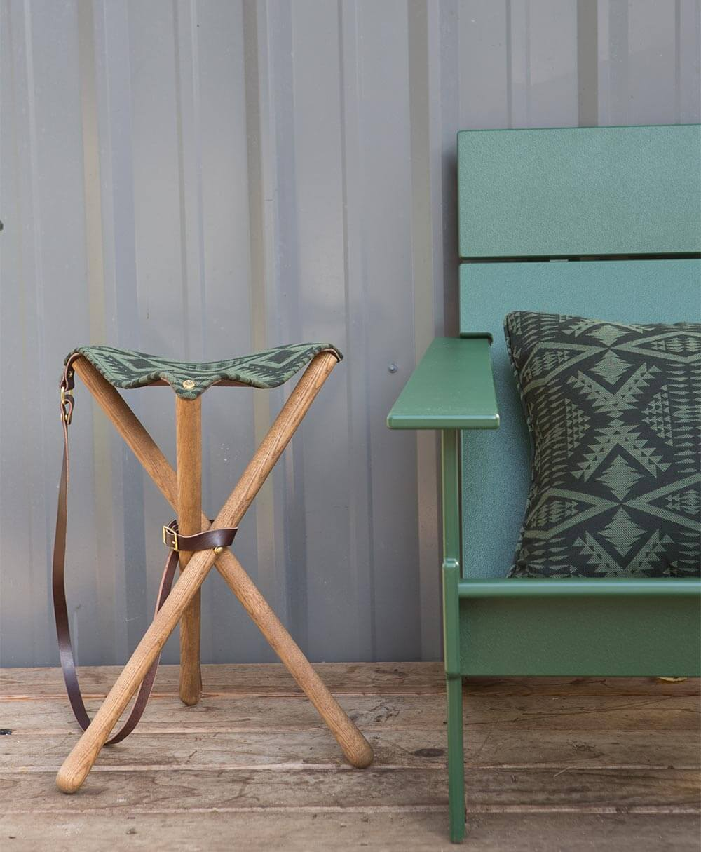 A stool featuring a green patterned upholstery fabric from the Pendleton by Sunbrella collection sits next a green pillow.