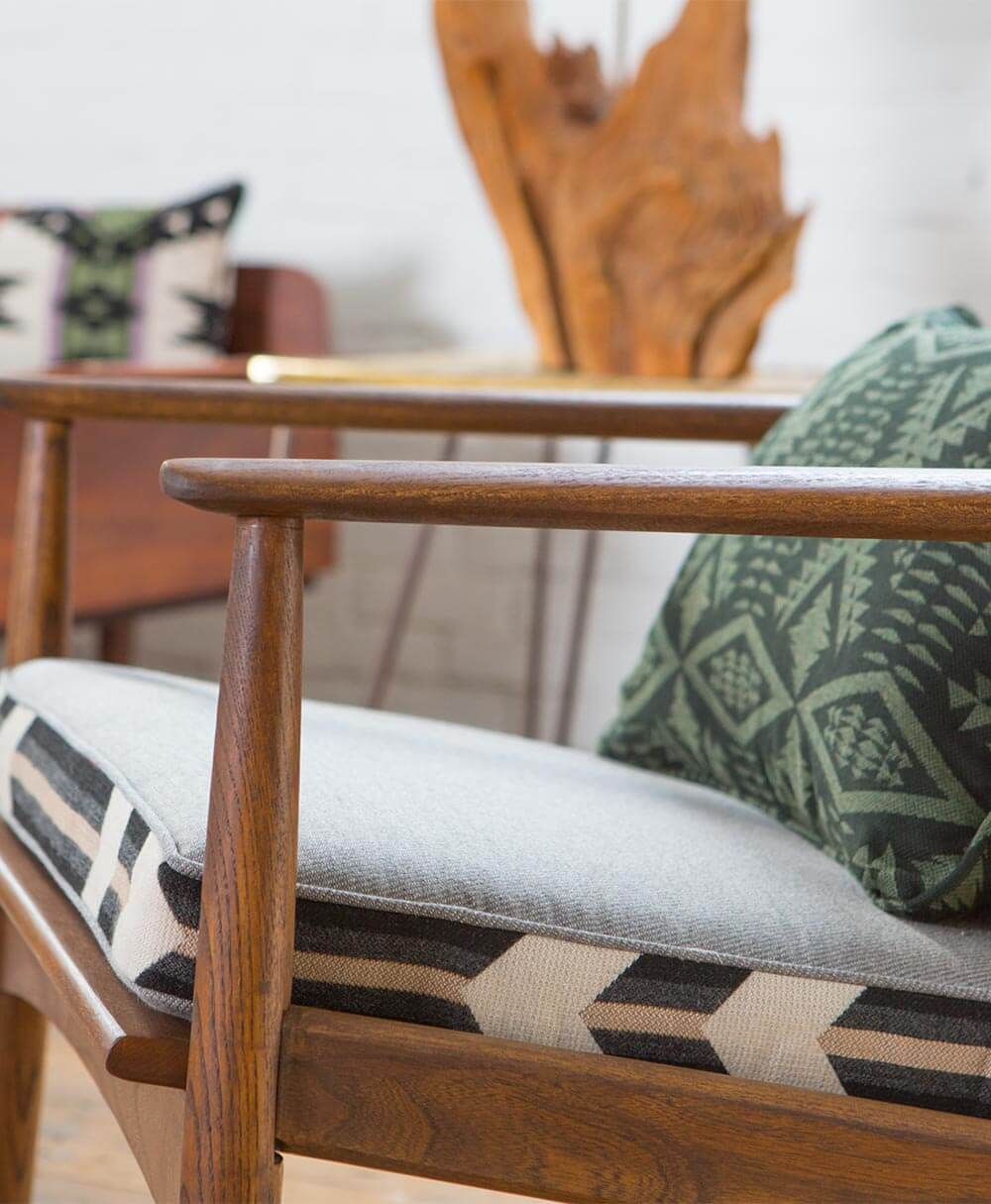 A wooden chair with a grey cushion and green patterned pillow, made using Pendleton by Sunbrella upholstery fabrics.