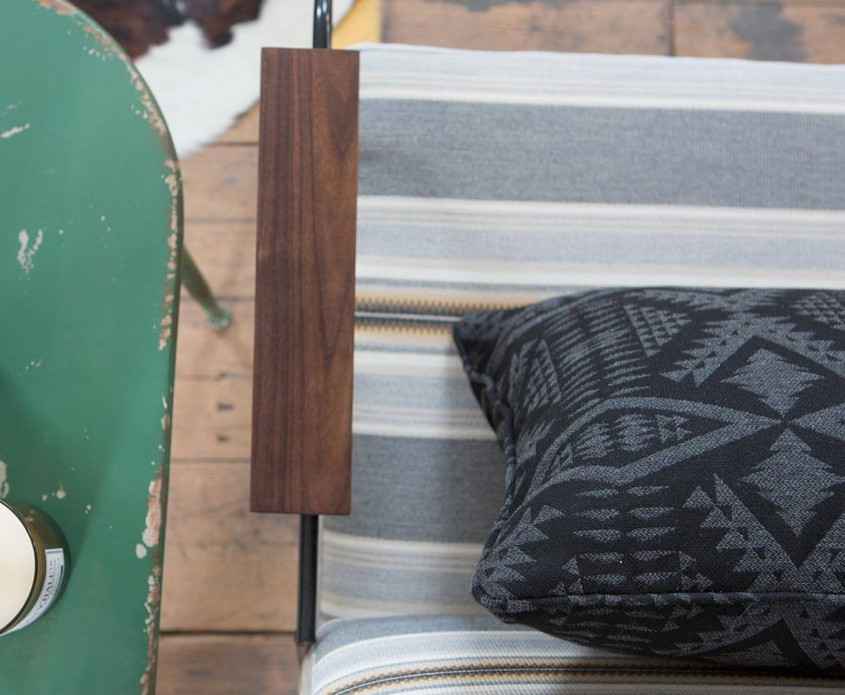 A grey striped chair is shown with a black and grey patterned pillow.