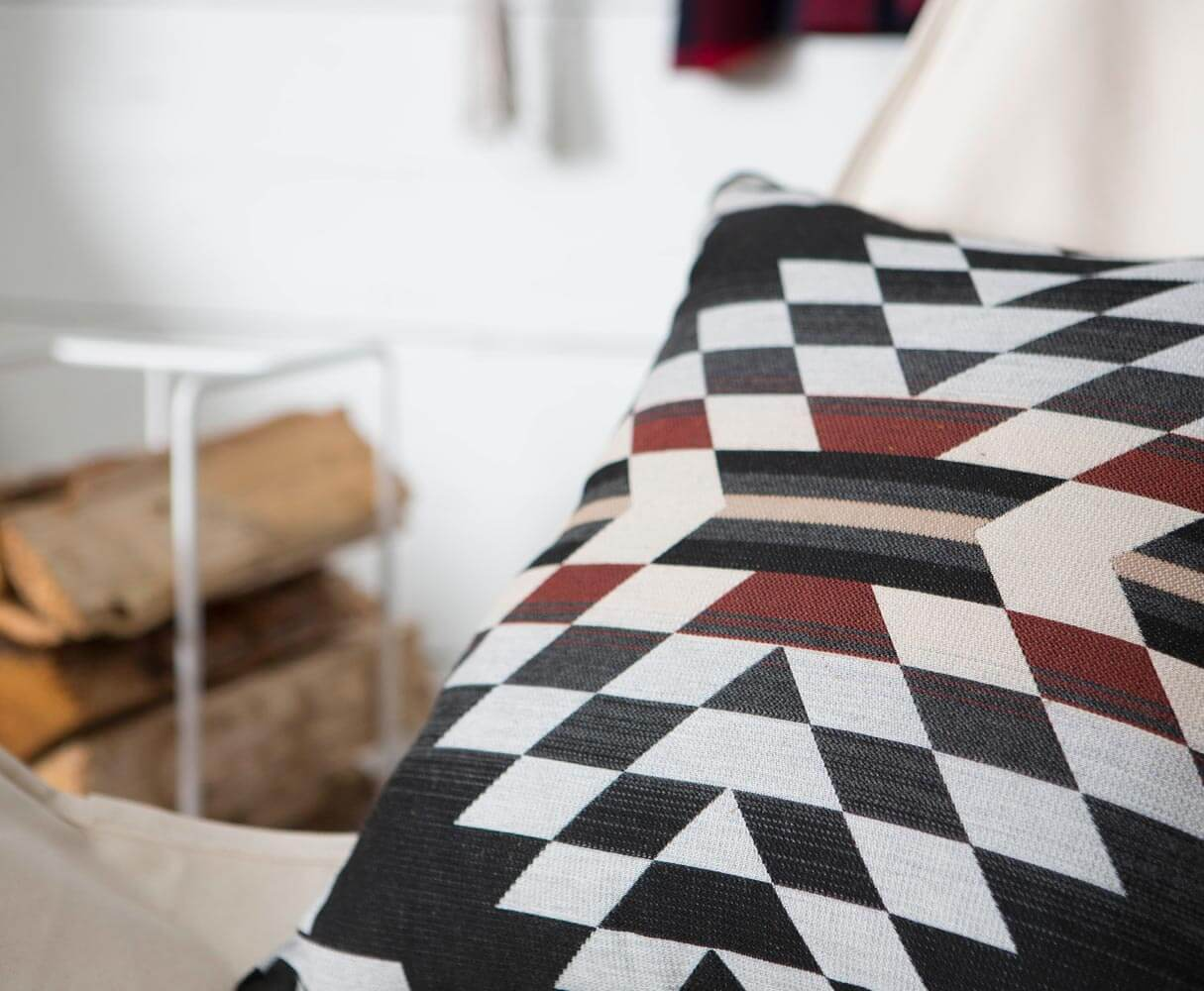 Close up view of a black and red patterned Pendleton by Sunbrella fabric.