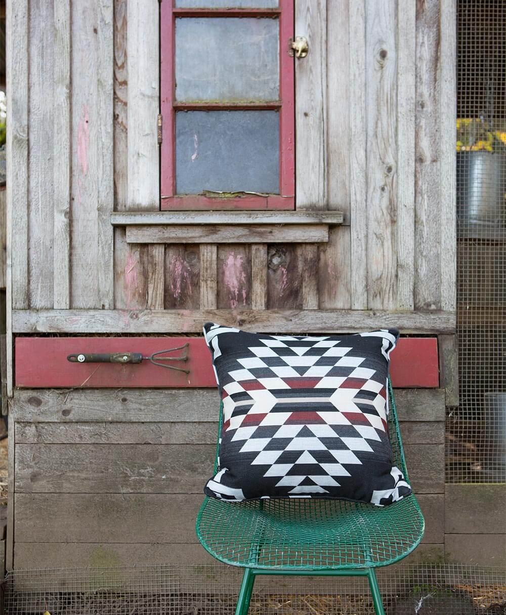 A large pillow made using a black and red pattern from the Pendleton by Sunbrella fabric collection sits outside on a chair.