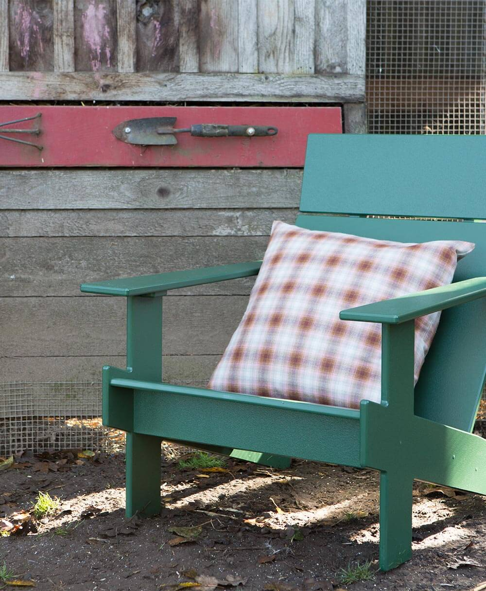 A plaid pillow from the Pendleton by Sunbrella upholstery collection sits on a green adirondack chair.