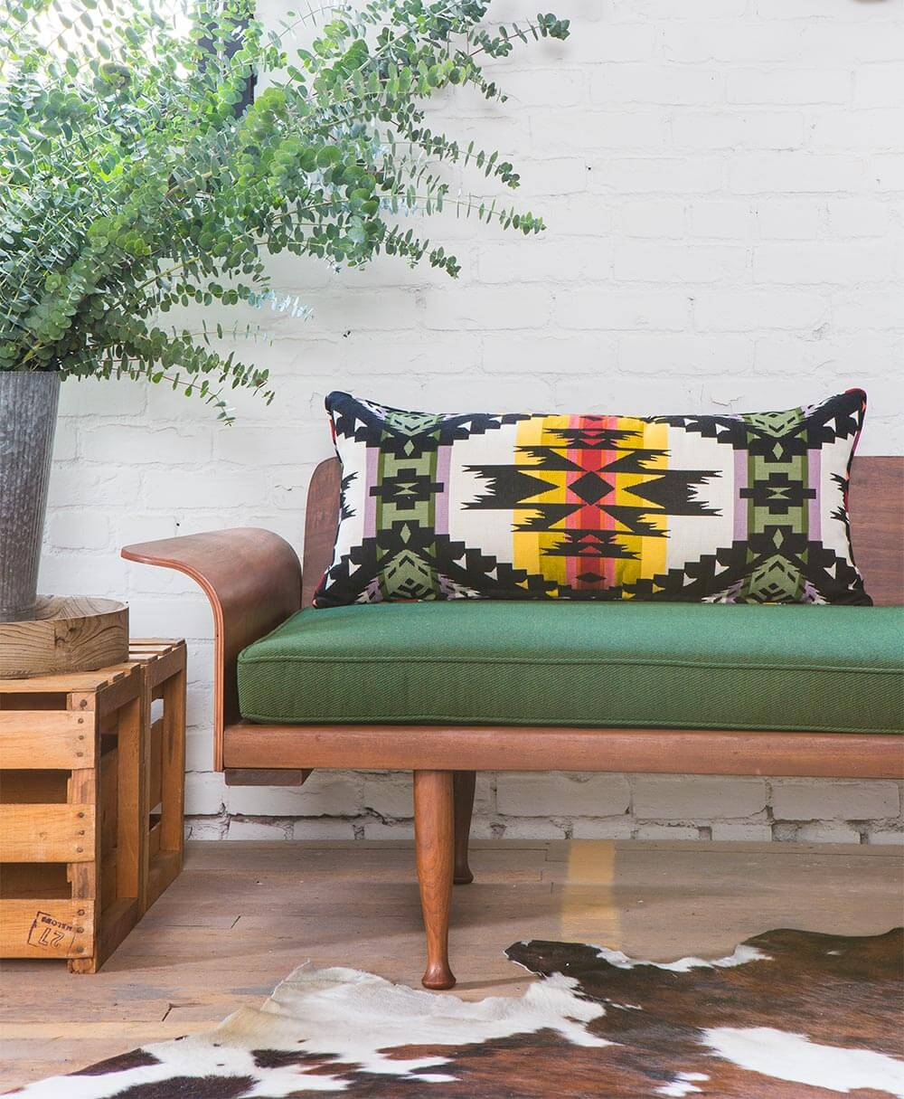 A close up of a wooden sofa with bright green cushion made using Pendleton by Sunbrella fabric.
