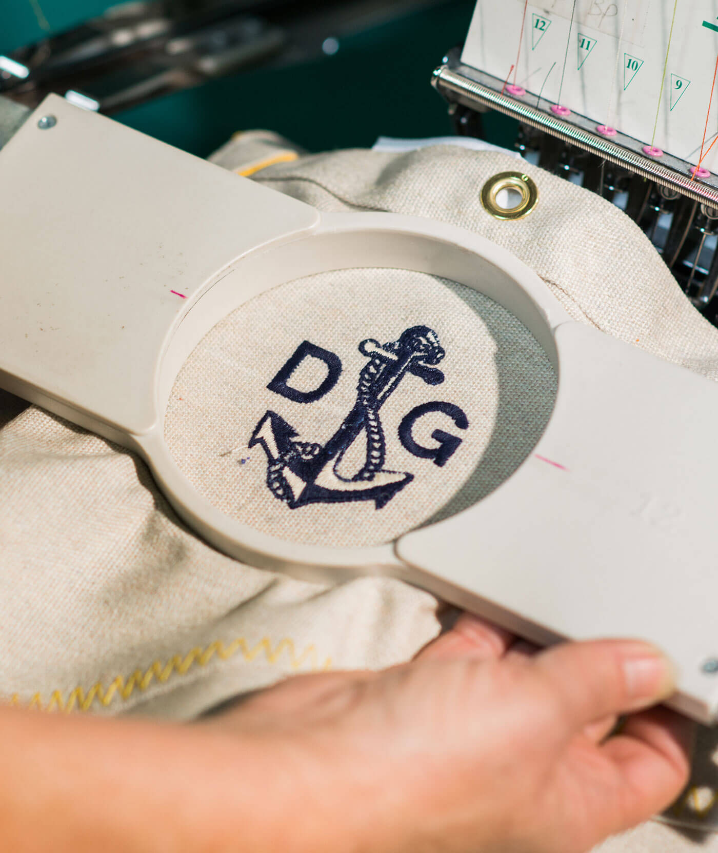 Initials being embroidered onto a canvas bag