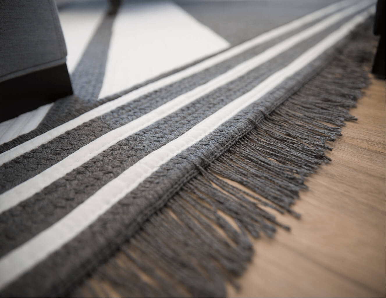 A grey Sunbrella Rug by Colonial Mills featuring a white detailing on the edge