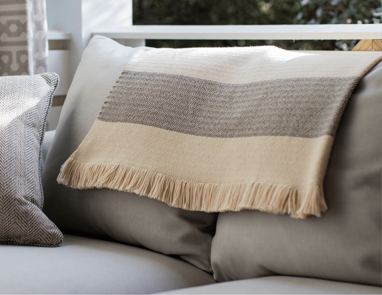 A Beige Sunbrella Throw with Grey Detail draped over a grey sofa