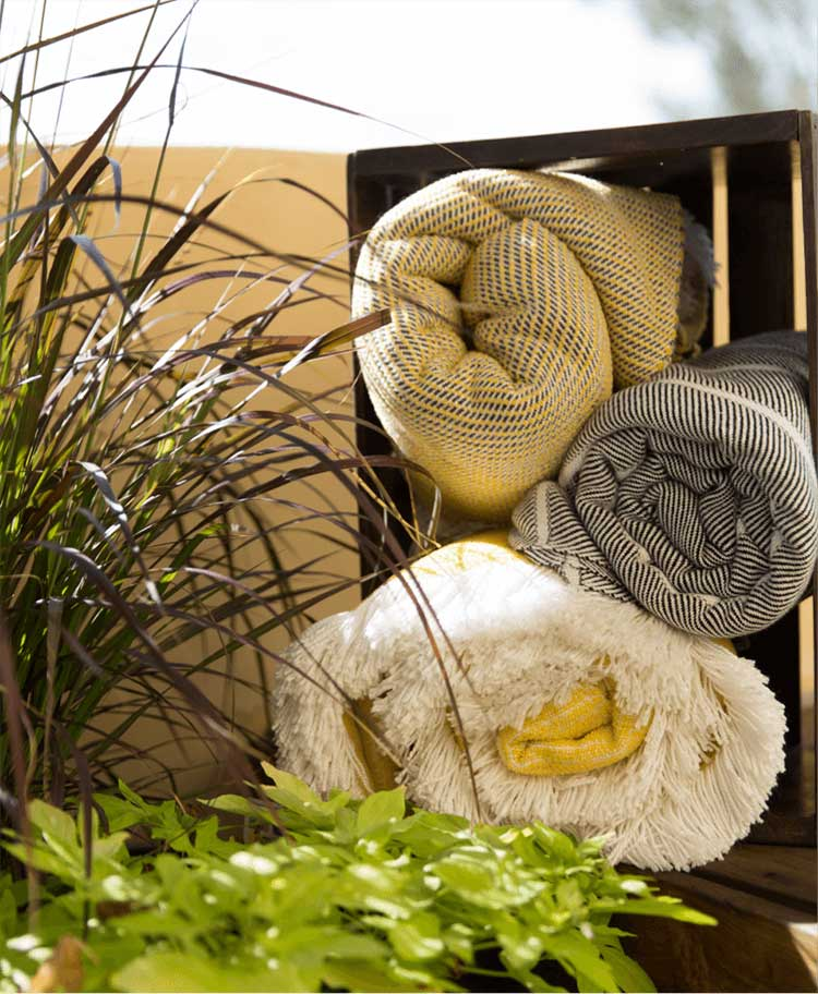 Three Sunbrella Throws are rolled up and on display in a wooden basket