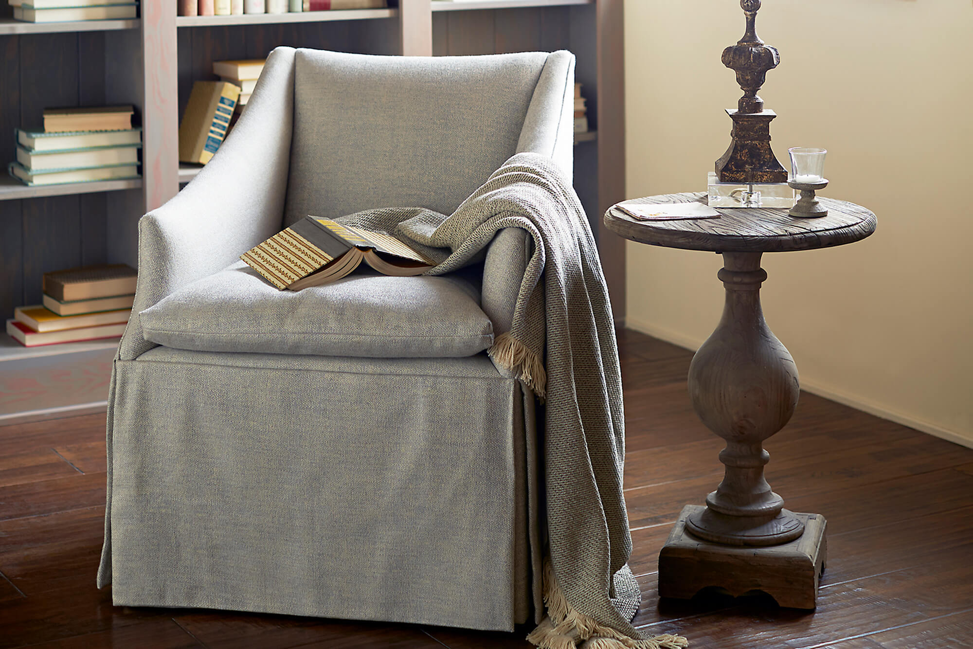 A Sunbrella Throw by Textillery Weavers is draped over a grey chair