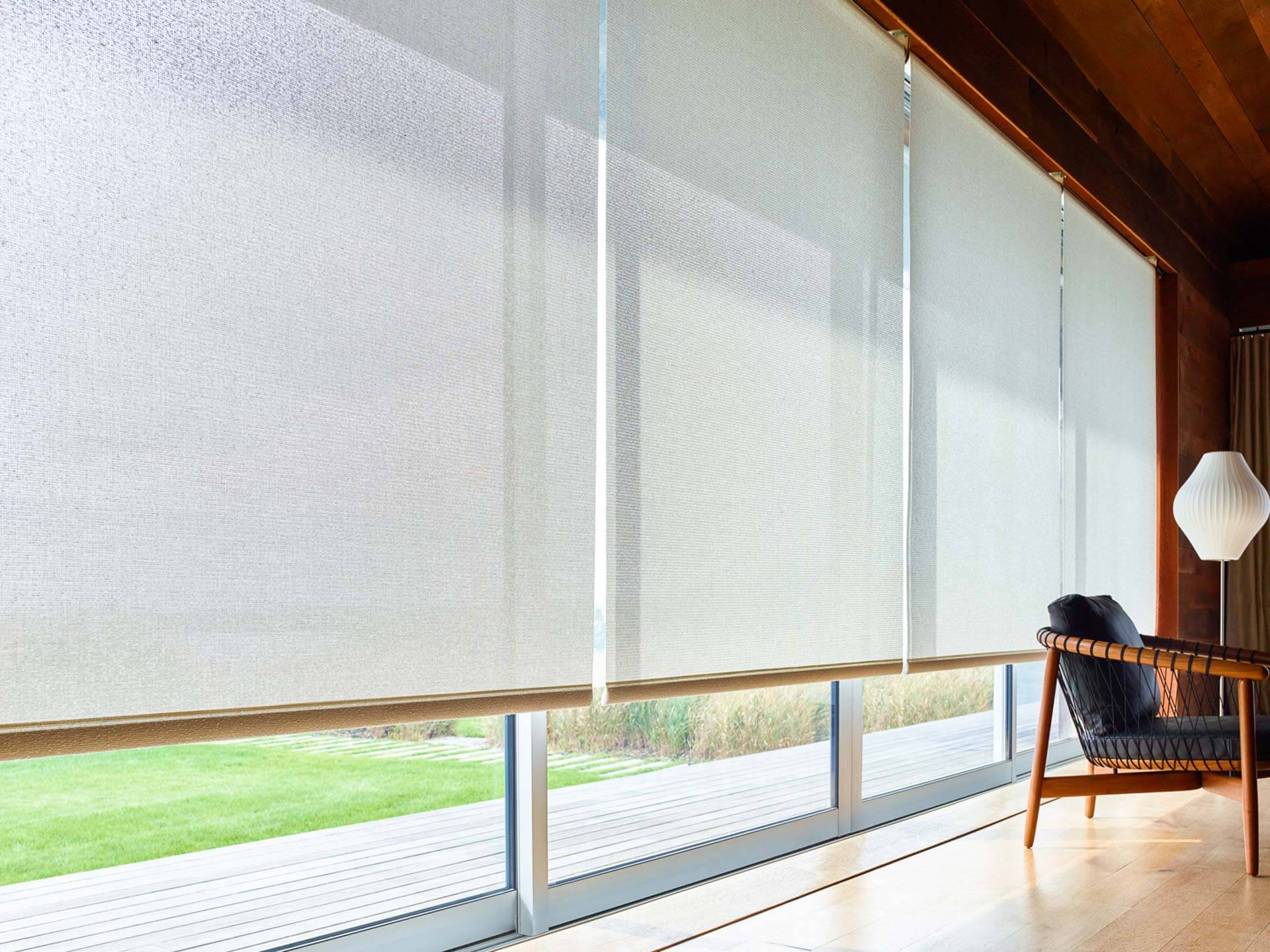 A modern living room featuring Solar Shades from the Shade Store