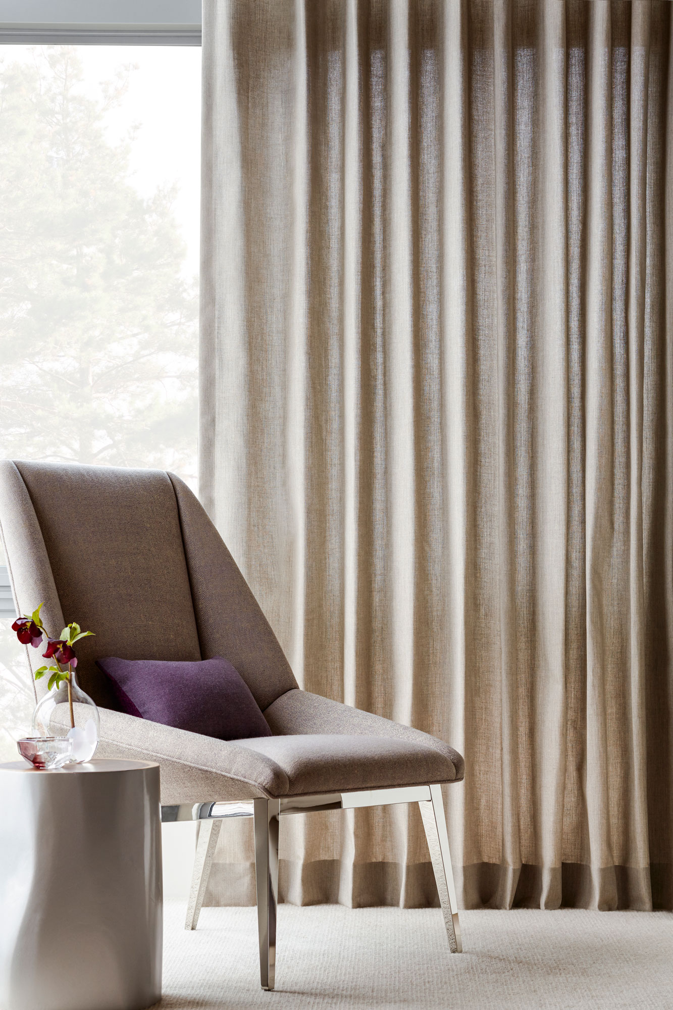 Detail of a neutral Sunbrella upholstered chair in the master bedroom, with neutral Sunbrella drapery from The Shade Store behind it.