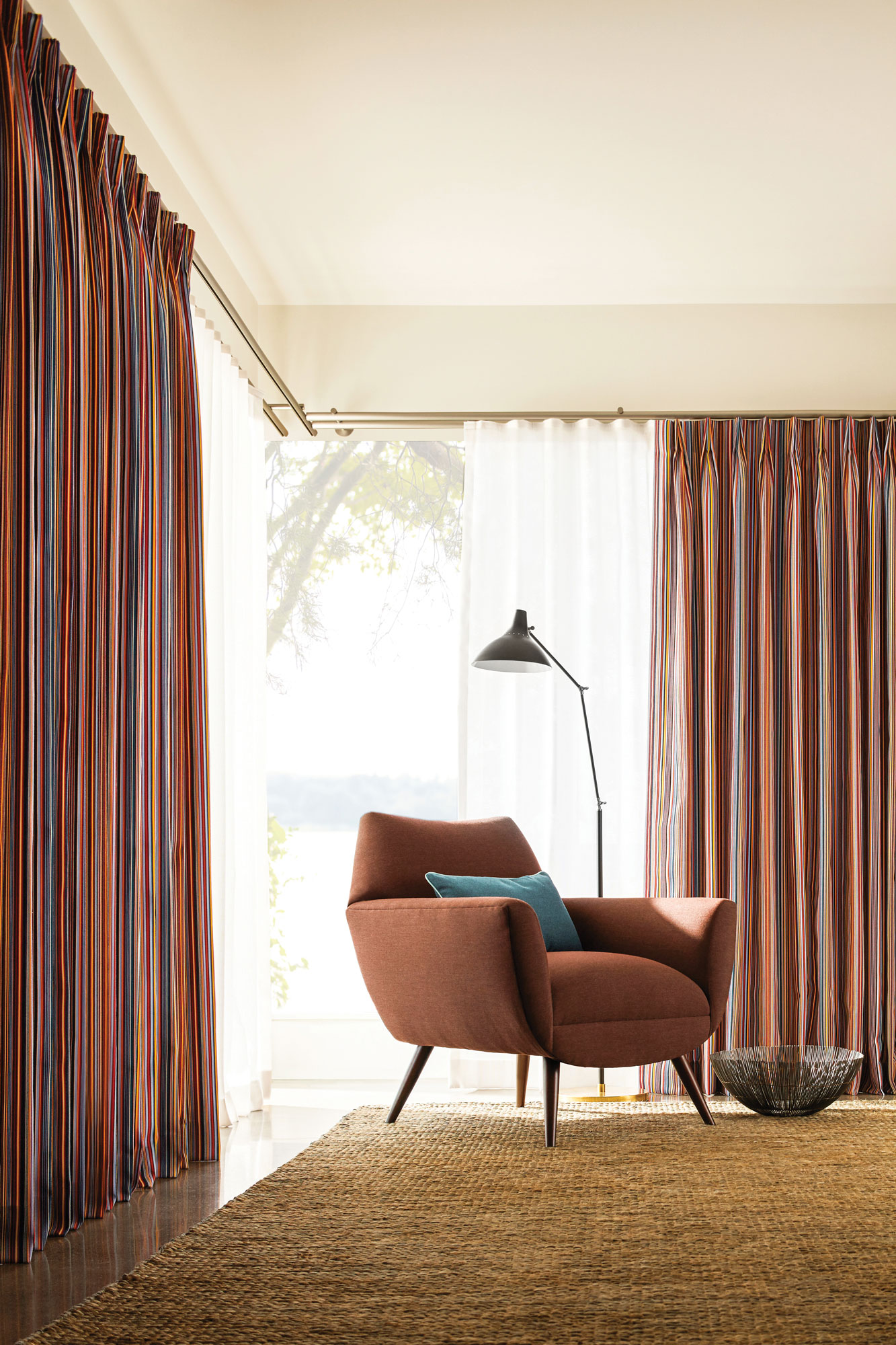 A family room decorated in earth tones, with a Sunbrella upholstered retro chair and Sunbrella striped drapery from The Shade Store.