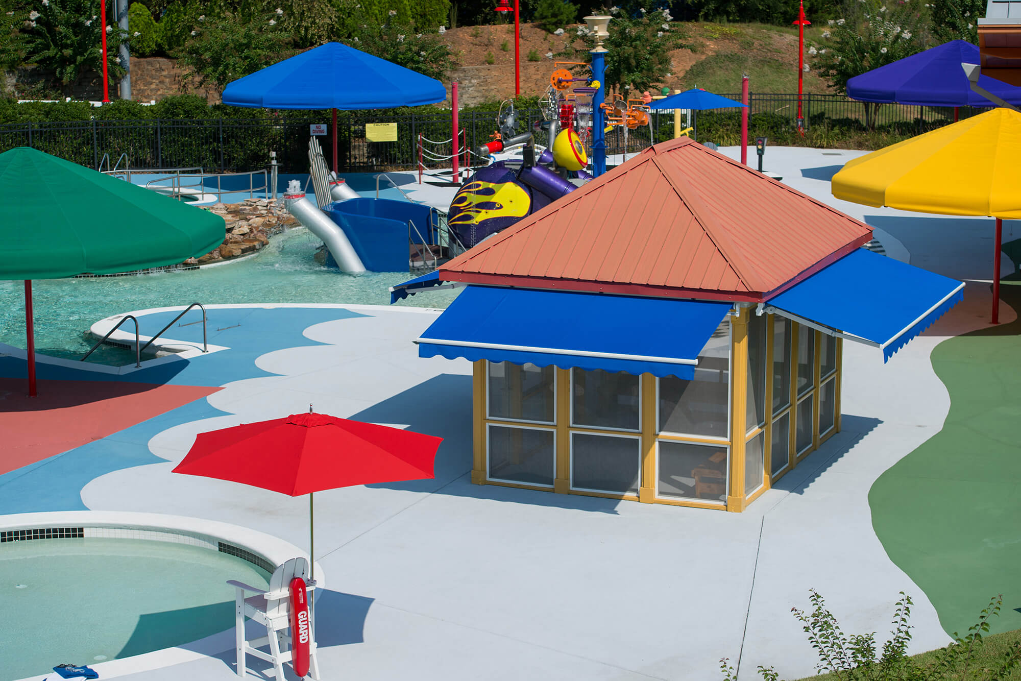 A waterpark offers shade with brighly colored umbrellas and bold blue retractable awnings