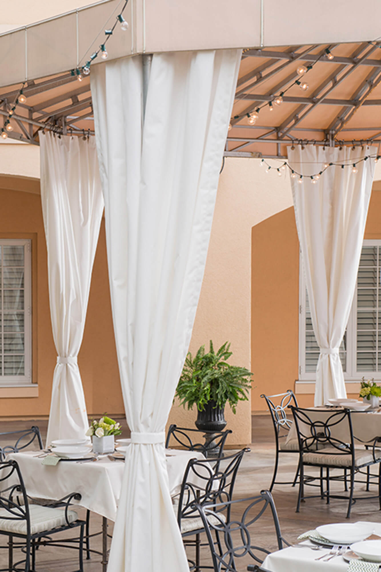 A restaurant patio is shaded by a fixed frame awning made using beige Sunbrella Clarity fabric.