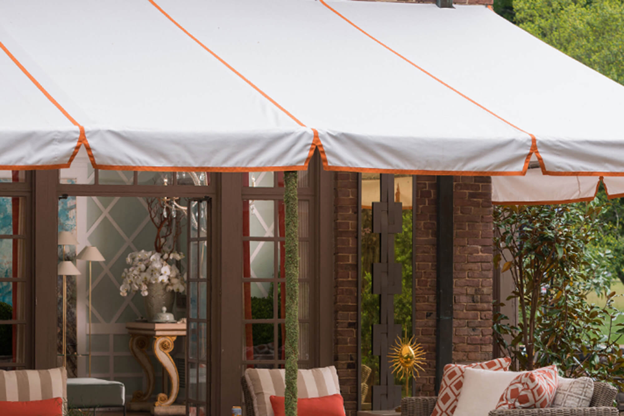 A patio is shaded by a fixed frame awning with white Sunbrella fabric and orange trim