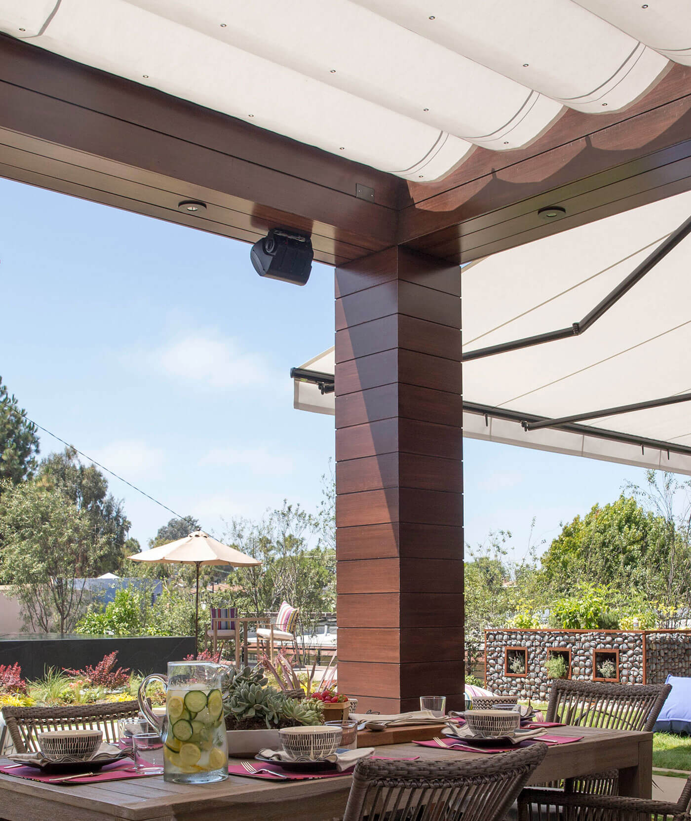 A patio is shaded by a pergola and retractable awning made with Sunbrella fabrics