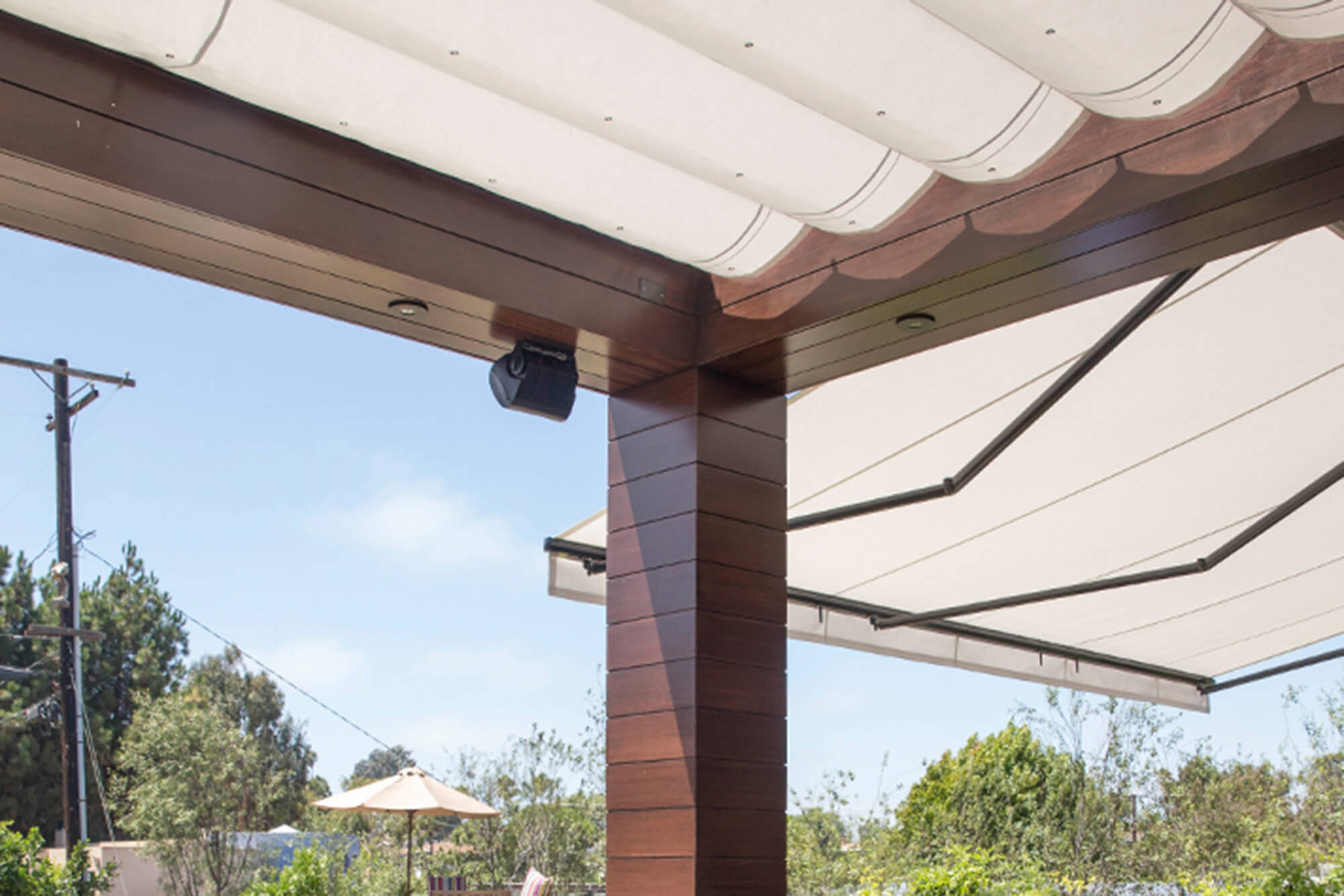 A patio is shaded by a retractable awning and pergoal both made using Silver Sunbrella shade fabric