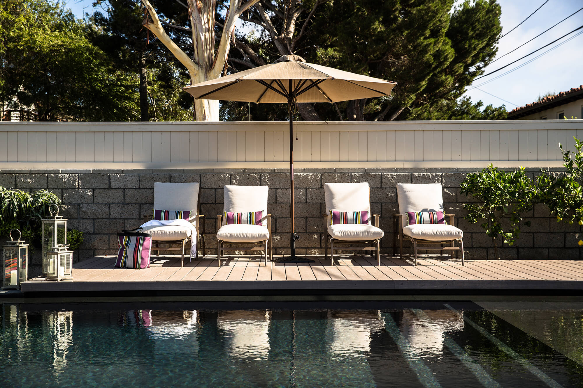A beige umbrella made using Sunbrella fabrics shades lounge chairs next to the pool