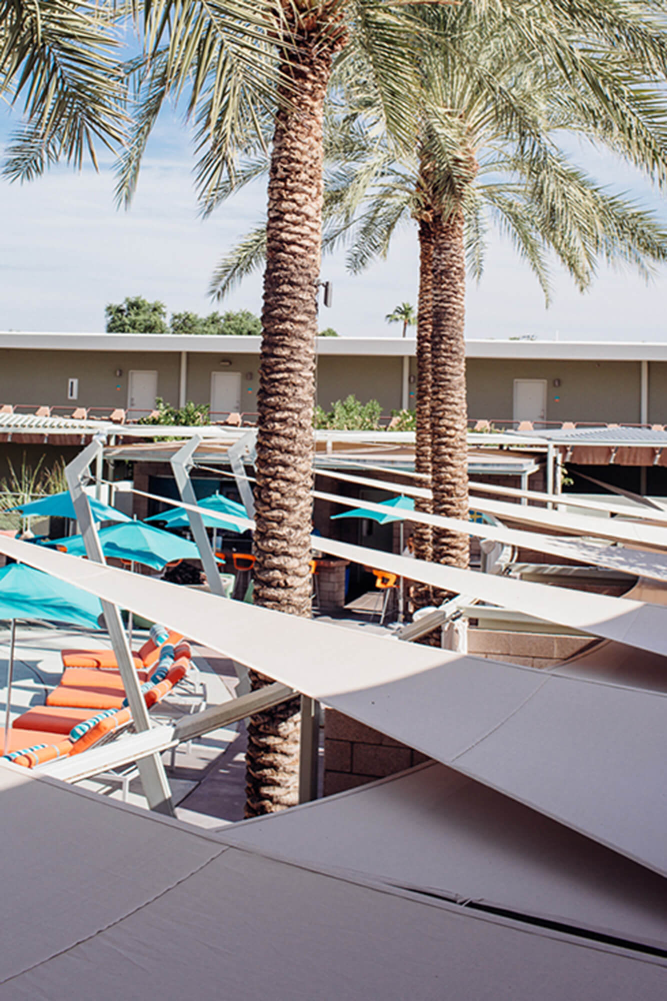 A hotel's poolside lounge chairs are shaded by beige shade sails made using Sunbrella Contour fabric