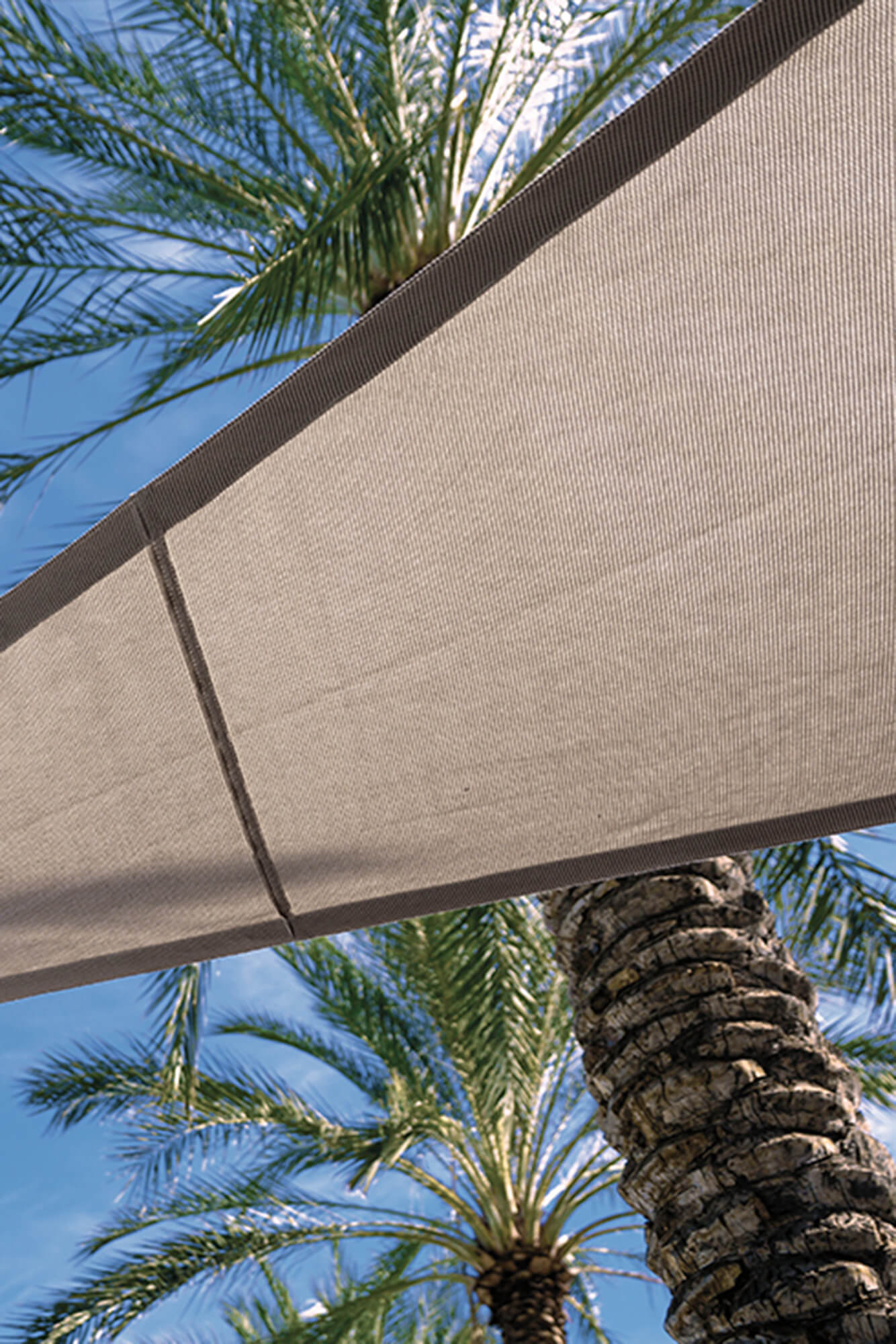 Detail of the underside of a beige shade sail made using Sunbrella Contour fabric
