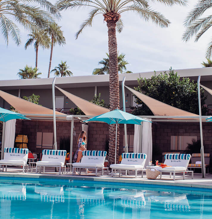 Lounge chairs poolside are shaded by beige shade sails made of Sunbrella Contour fabric and bright teal umbrellas
