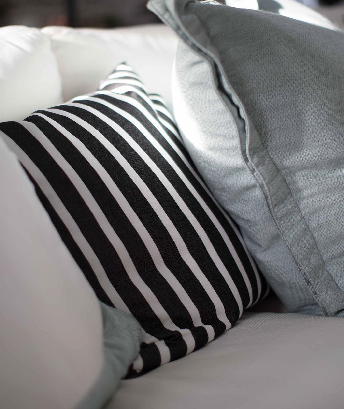 Un divano da interni con cuscini jacquard dai colori neutri e gialli