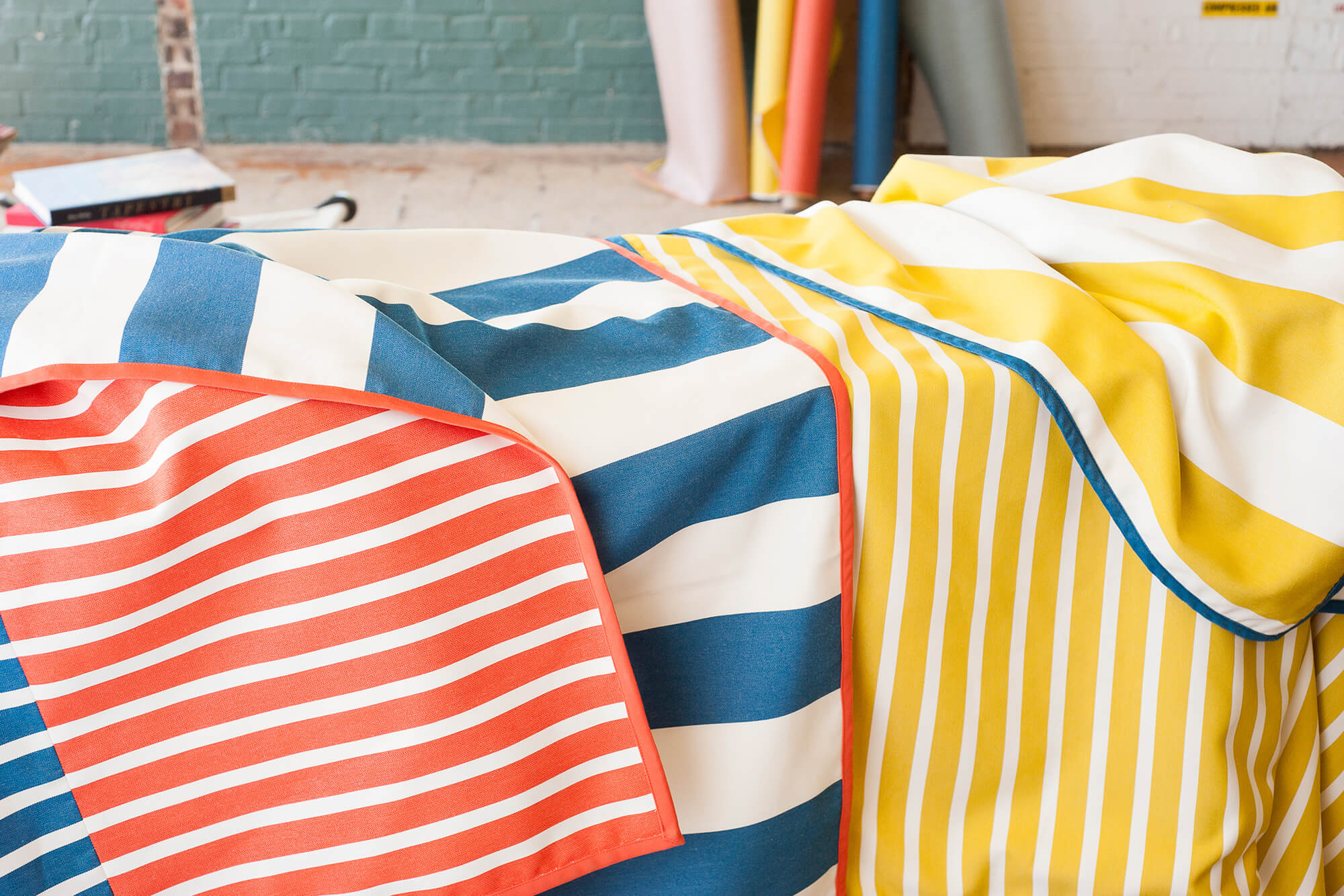 Draped fabrics in bright yellow and white, blue and white, and red and white stripes