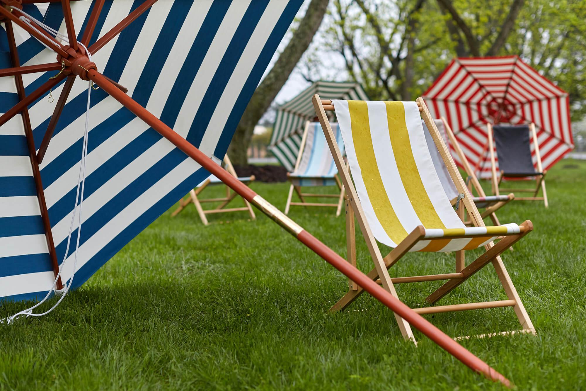 ผ้าลายทางคาบานาบนเก้าอี้คาบานาและร่มตั้งอยู่บนสนามหญ้า