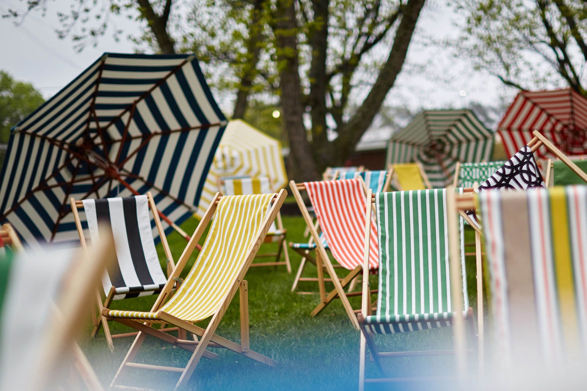 Brightly colored striped cabana chairs and umbrellas sit on the lawn