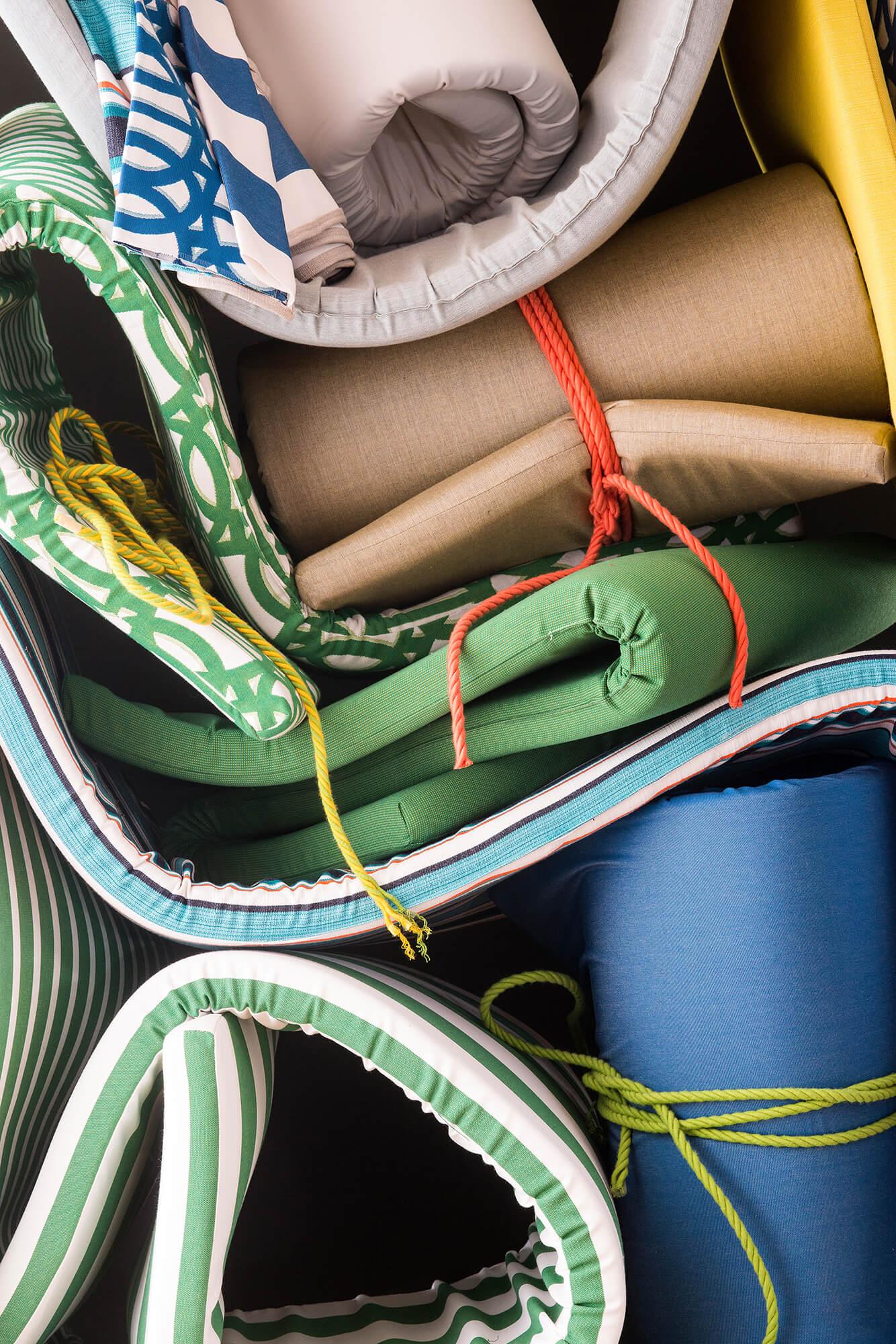 เบาะสีสว่างมากมายวางเรียง พับ และมัดเข้าด้วยกันด้วยเชือกถัก Sunbrella