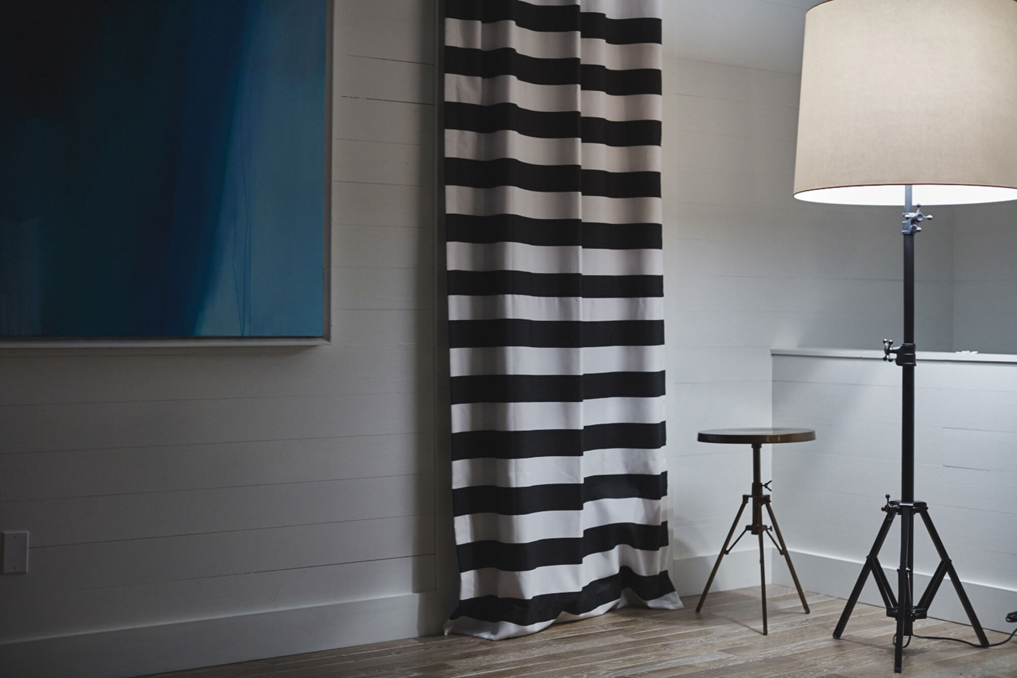 A living room gets a bold look with black and white striped drapery