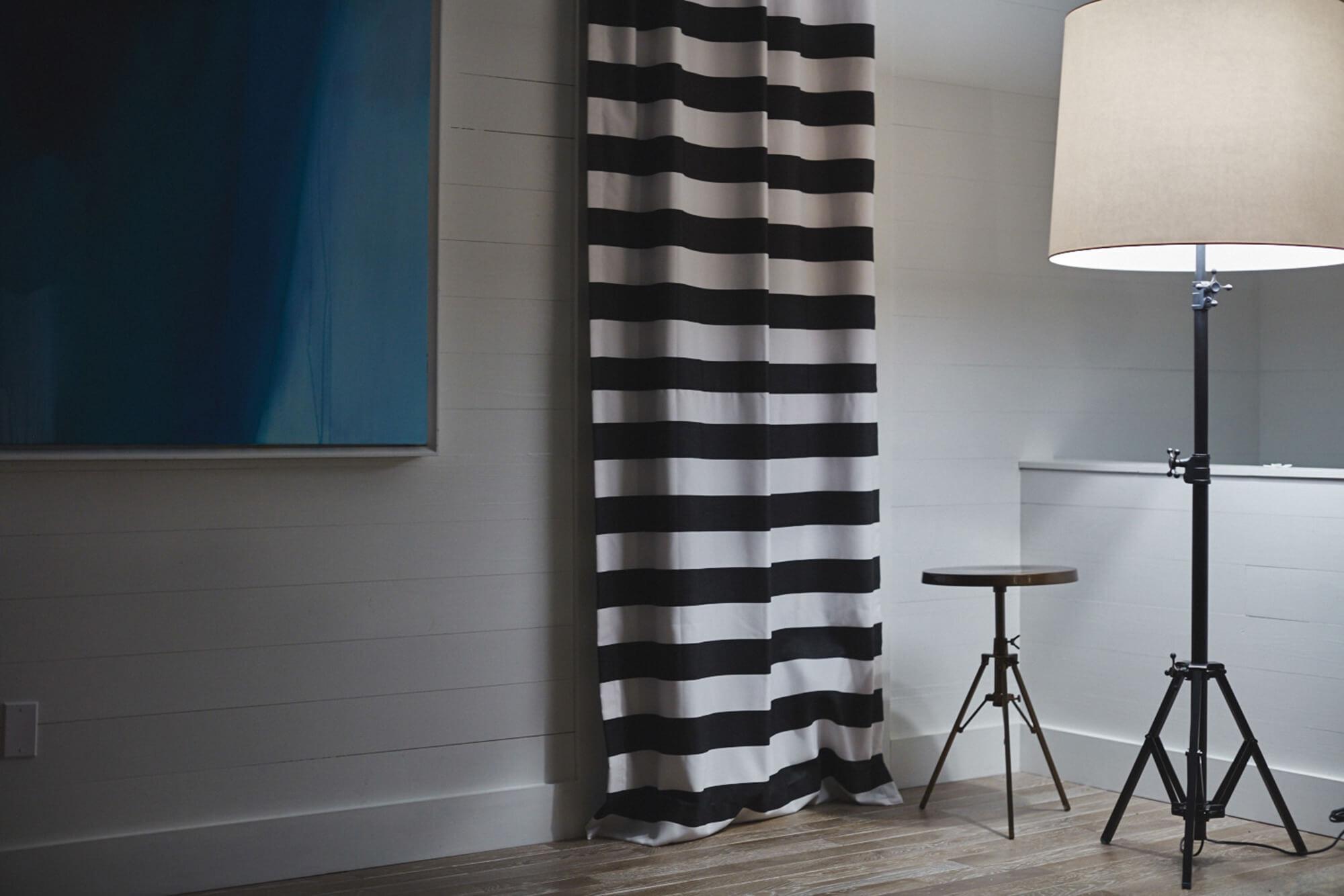 Un soggiorno guadagna un aspetto audace grazie alle sue tende a strisce bianche e nere