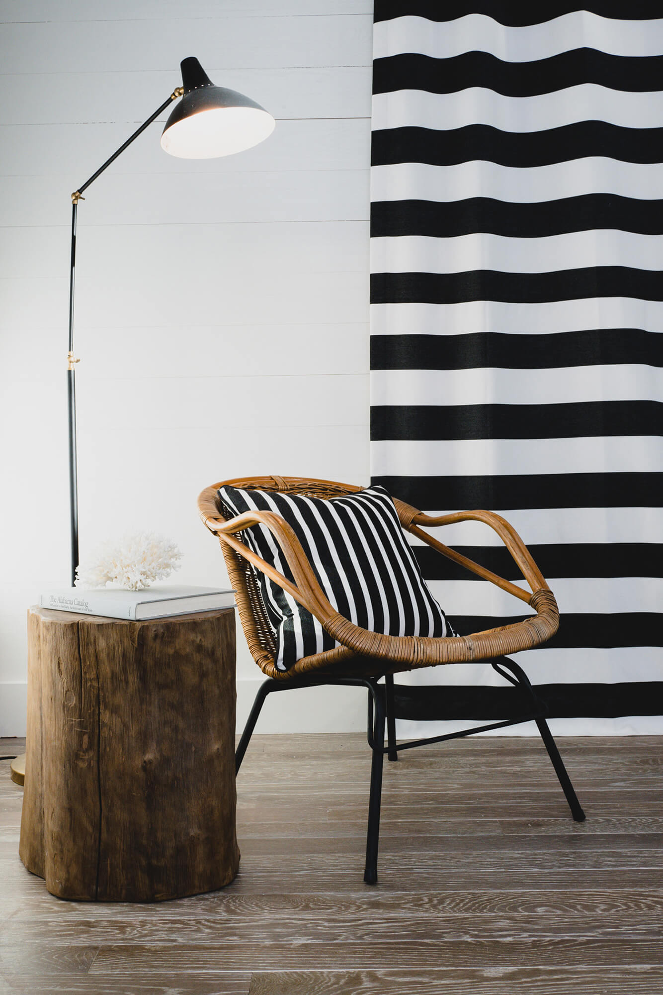 Chair with black and white striped pillow with black and white striped drapes in the background