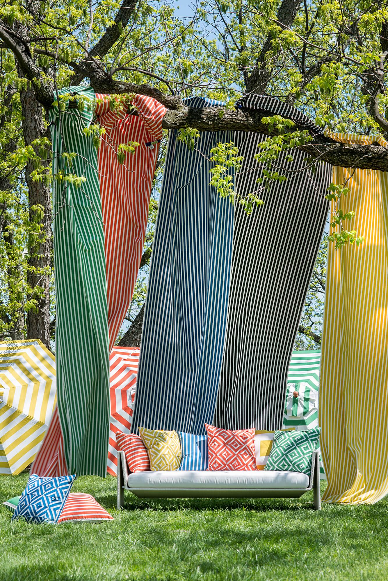 Ombrelloni, cuscini e tessuti fluttuanti in strisce chiare di rosso, blu e giallo