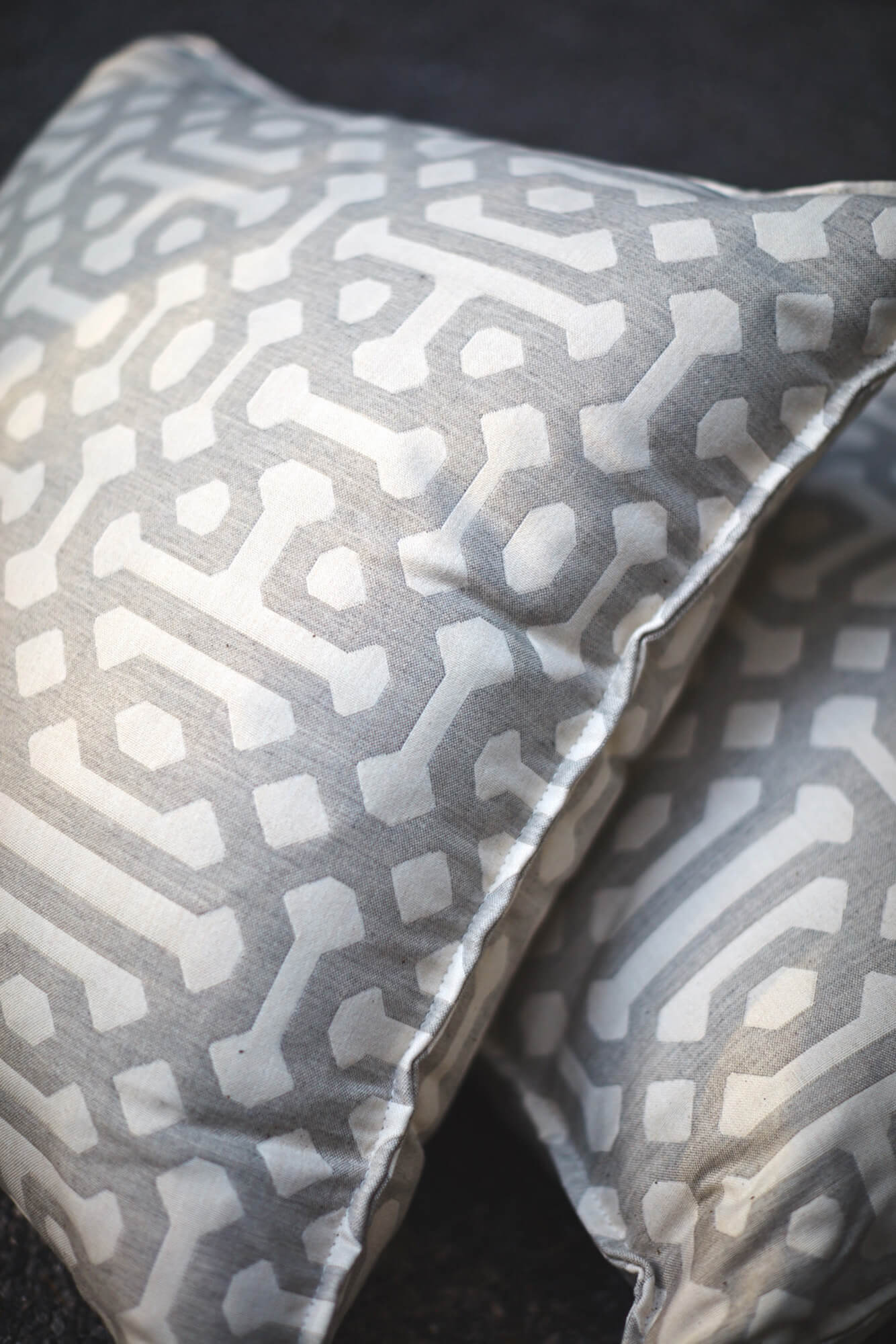 Due cuscini realizzati usando il tessuto per tappezzeria Sunbrella Fretwork Pewter