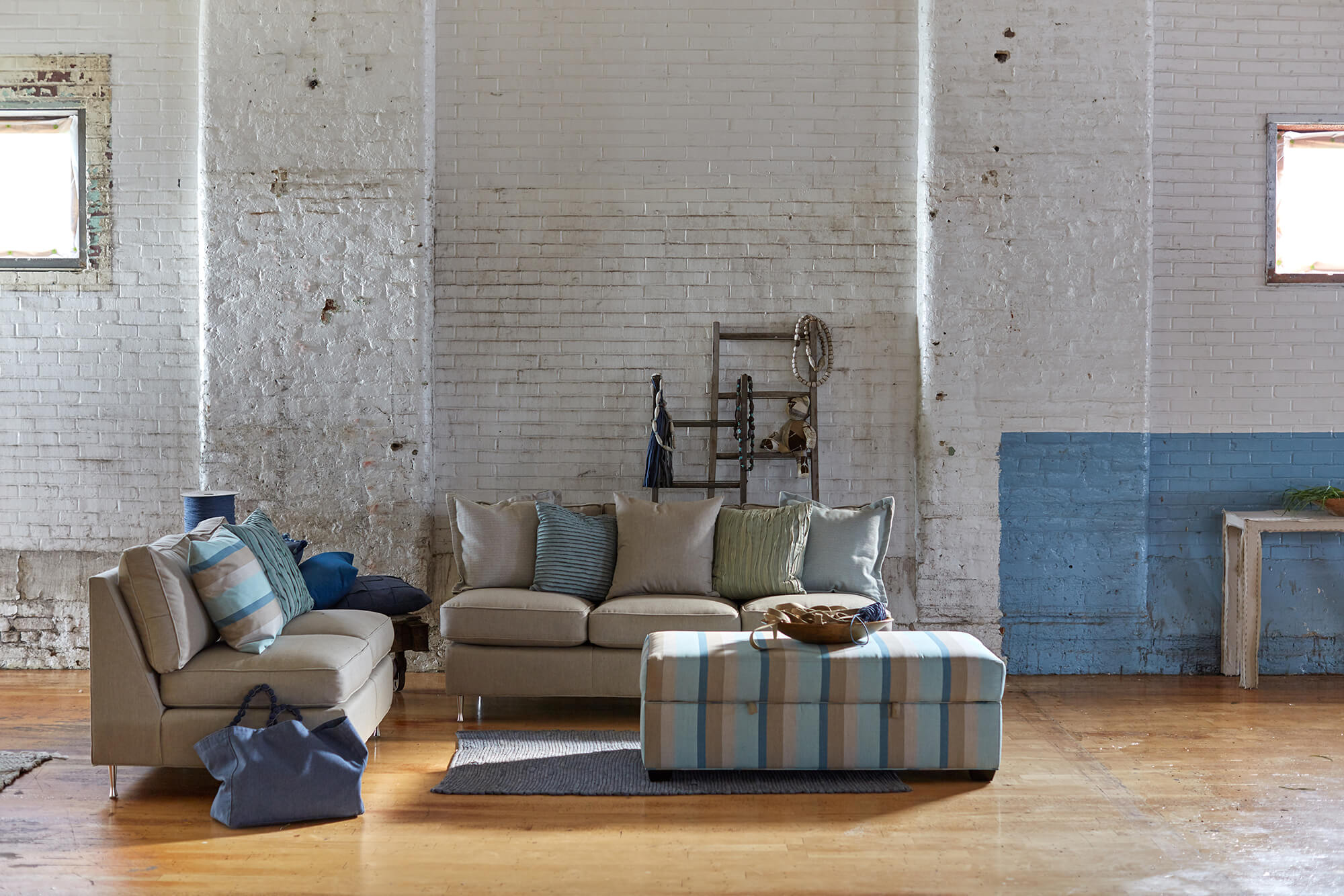 Neutral sofas are complemented with a large upholstered ottoman with blue striped Sunbrella fabric