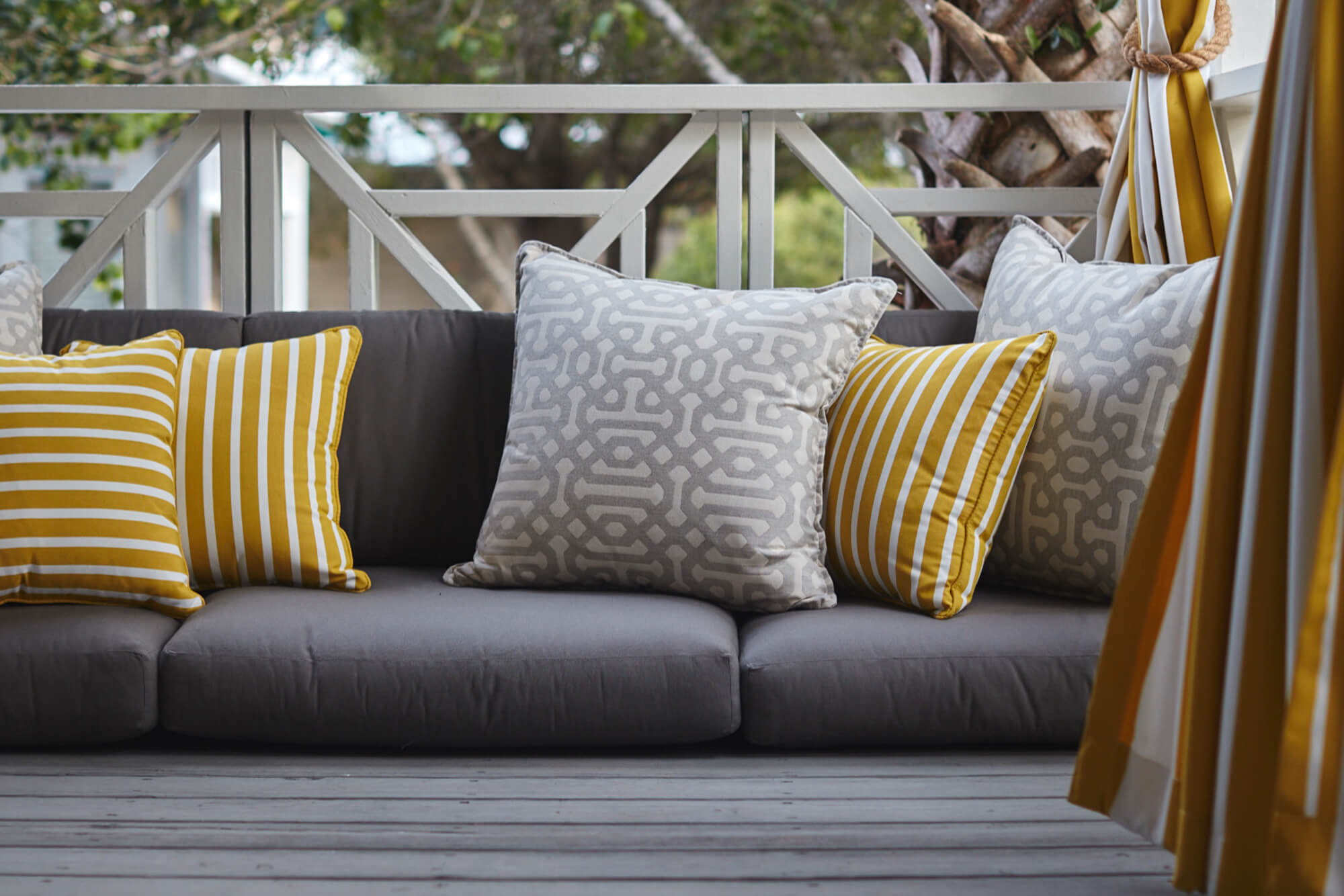 Grey cushions on a patio with grey and yellow throw pillows