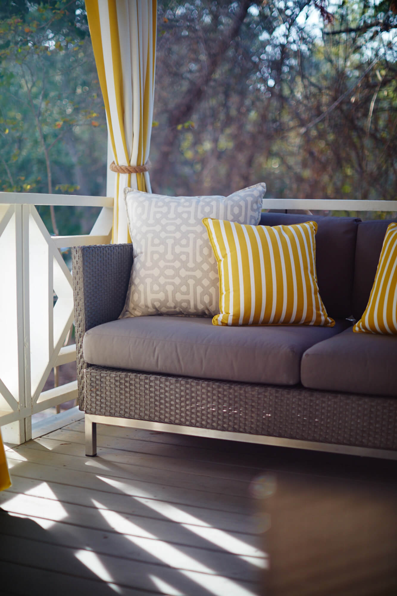 A patio with grey sofa gets a pop of color from yellow striped pillows and drapery