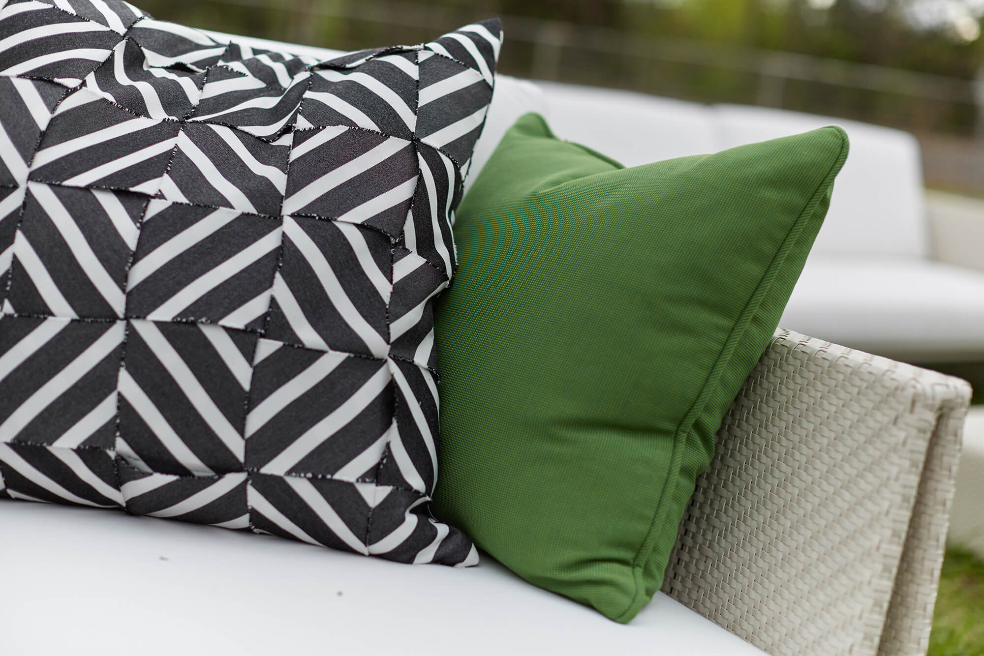 Pillows made of green Sunbrella upholstery fabric and black and white striped Sunbrella fabric