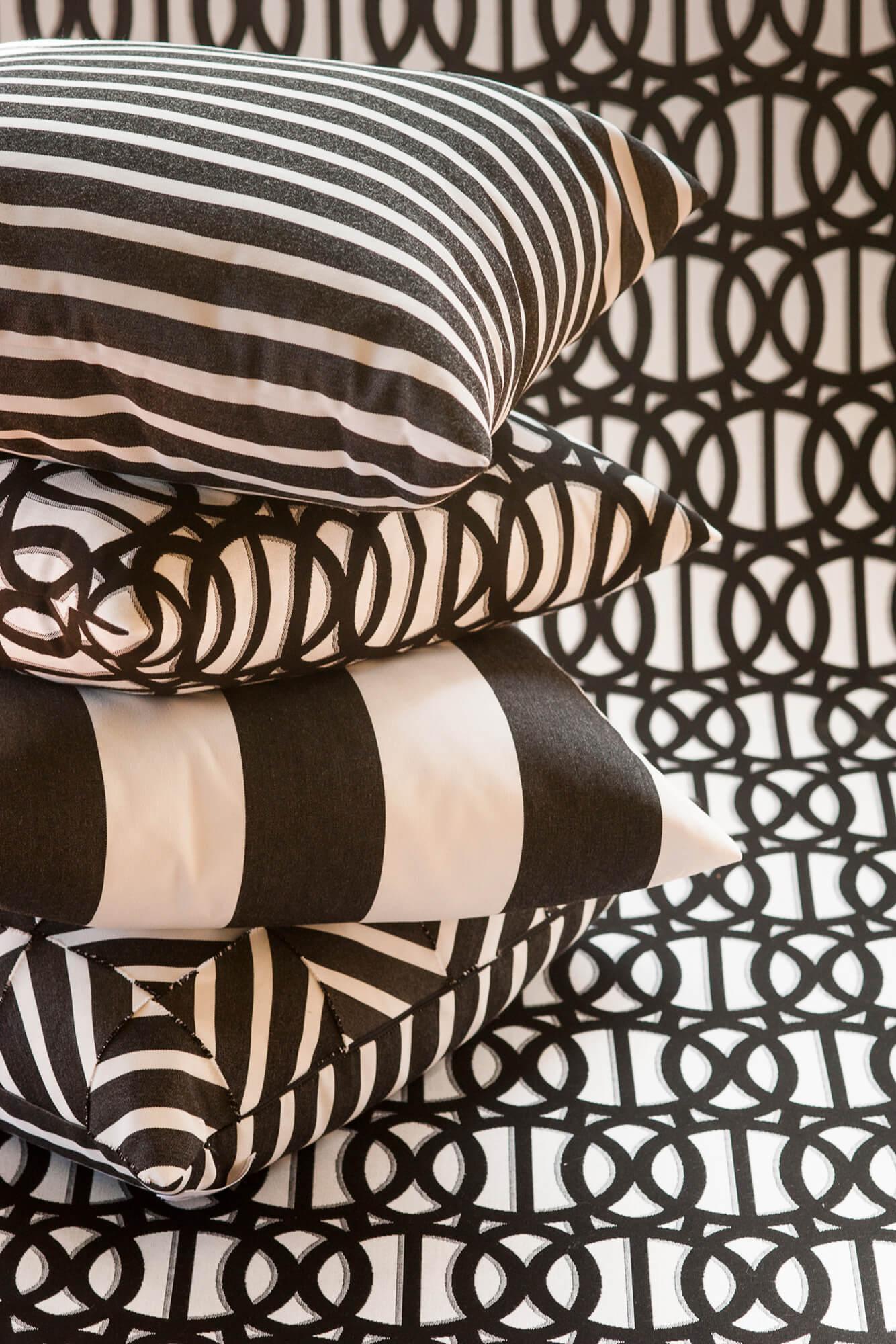กองหมอนสีขาวและดำตัดกับพื้นหลังผ้าแจ็คการ์ดสีขาวและดำ