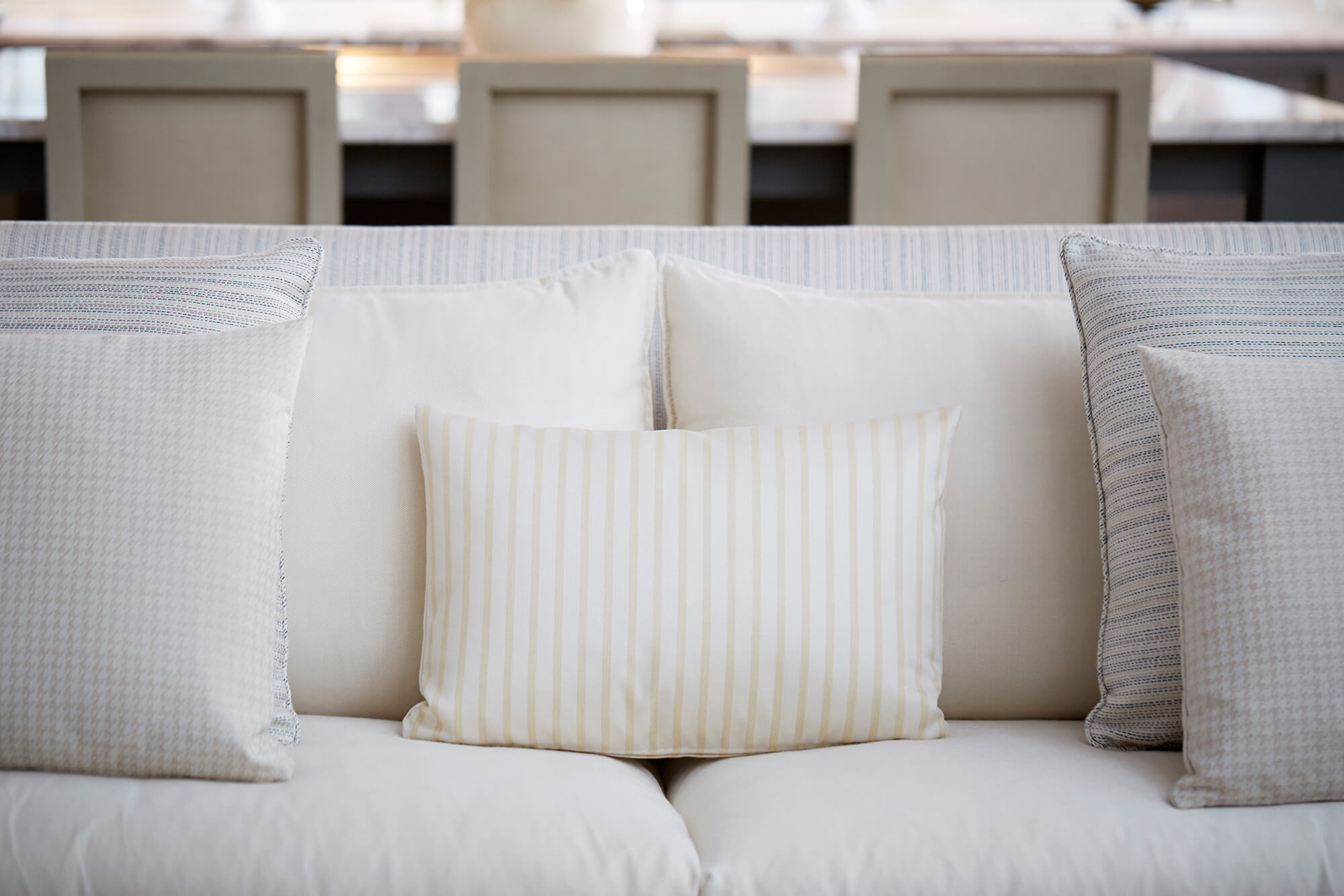 Close up of throw pillows in neutral colored textures decorating a sofa